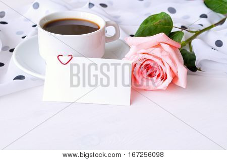 St Valentines day background - cup of coffee rose blank love card in pastel tones. St Valentines day still life with card for St Valentines day message