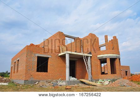 House under construction. New brick building house construction with doorway columns windows balcony. Building site.