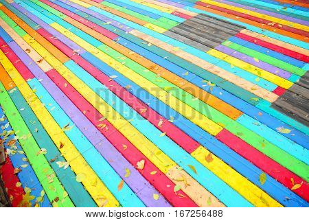 Colorful Wooden Background with Autumn Leaves.The seven colors are red orange yellow green blue indigo and violet. In general rainbow colors represent diversity and acceptance.
