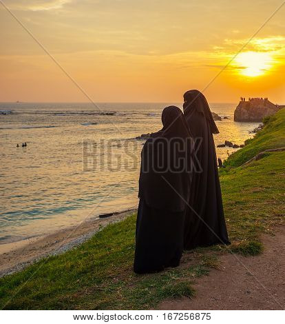The muslim women stand on the wall of Galle Fort at the ocean's coast and watch the sunset Sri Lanka.