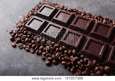 Chocolate and coffee beans .Dark chocolate background. A large bar of chocolate on gray abstract background. Background with chocolate. Sweet food photo concept. Copyspace