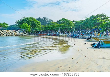 GALLE SRI LANKA - DECEMBER 3 2016: Most of the fishing boats come back to harbor after the midday and fishermen are busy with catch and nets on December 3 in Galle.