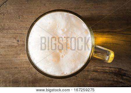 mug of beer on wooden table. top view