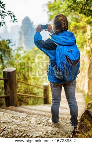 Young Female Tourist With Blue Backpack Taking Photo