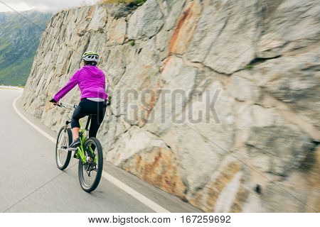 Young Woman Cycling. Shot taken in Switzerland, near Rhone Glacier and Furka Pass.