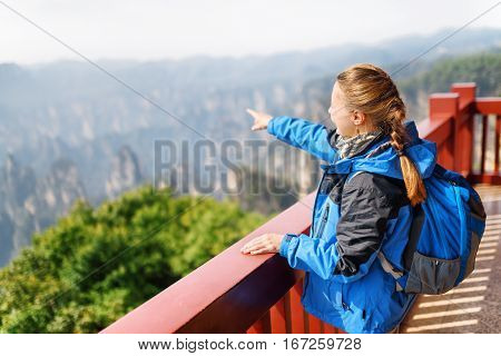 Young Female Tourist Pointing At Amazing Mountains