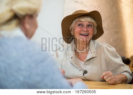 Smiling senior woman at table. Old ladies indoor. I have great news.