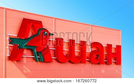 SAMARA RUSSIA - SEPTEMBER 30 2016: Auchan trade mark over blue sky background. French distribution network Auchan united more than 1300 shops
