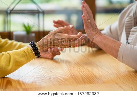 Hands of elderly women. Discussion at table. Understand and agree.