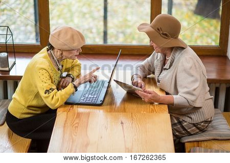Two senior women and laptop. Old ladies with tablet. Comparison of gadgets.