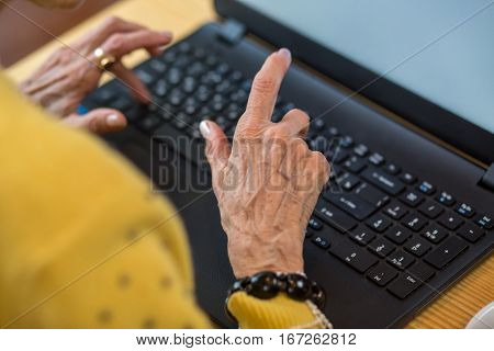 Elderly woman's hands and laptop. Notebook pc on table. Grandma typing a letter.