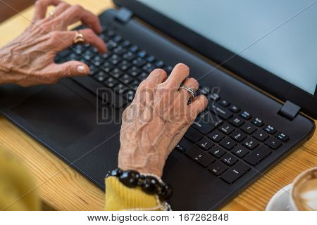 Old woman's hands and laptop. Pc keyboard of black color. Know more about modern technologies.