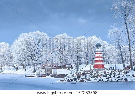 Navigation Lighthouse frozen water will shore frosted trees rime snow stone jetty pier tourist ship sunny day