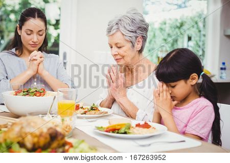 Mother and daughter with granny praying at dining table in home