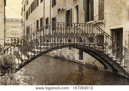 Vintage photo of the bridge in the Venetian canal (Venice Italy). The photo is intentionally polluted by spots in order to enhance the impression of old photos.