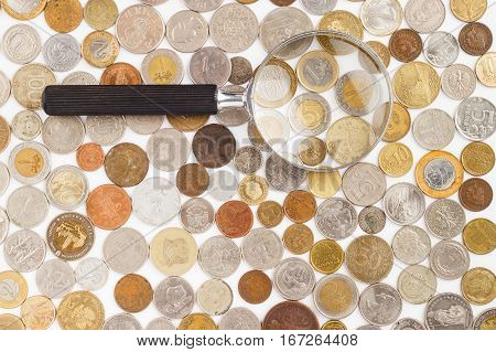 Different Collector's Coins And Magnifying Glass