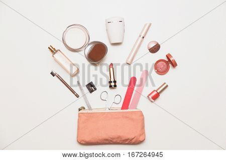 The contents of women's handbags. Make up bag with cosmetics. Top flat view