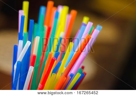 colorful drinking straws on the brown background