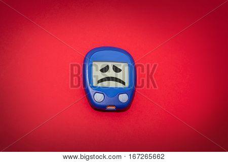 Sad Glucometer On Red Background