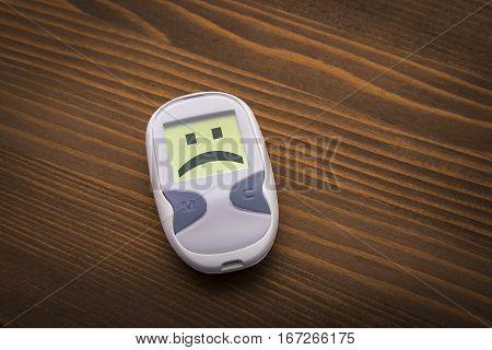 Sad Glucometer On Wooden Background