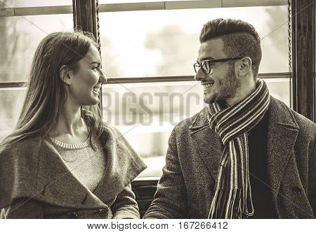 Happy young couple talking inside old vintage tram - Boyfriend and girlfriend smiling to each other - black and white edit - Focus on man's glasses