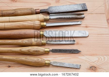 Old used wood lathe chisels selection on the wooden table selective focus