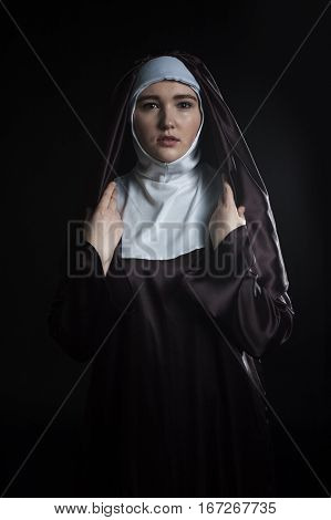 Front portrait of the young beautiful nun. Low key lighting. On black.