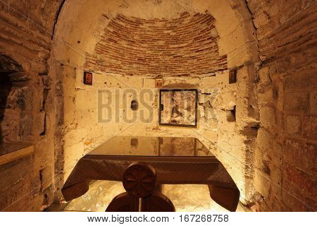 JERUSALEM, ISRAEL - MARCH 9, 2012: Interior of a hall in the Holy Sepulchre. Hall carved into the rock. Deep worth square table, covered with a cloth