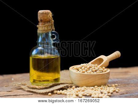 Soy bean and soy oil on wooden table.