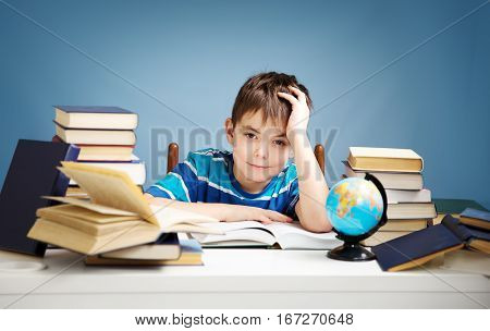 seven years old child reading a book at home. Boy studying at table on blue background