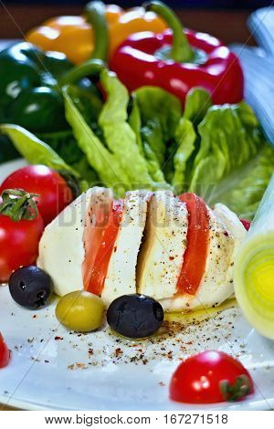 Healthy breakfast with tomato mozzarella olives seasoned with olive oil and vegetable pepper.