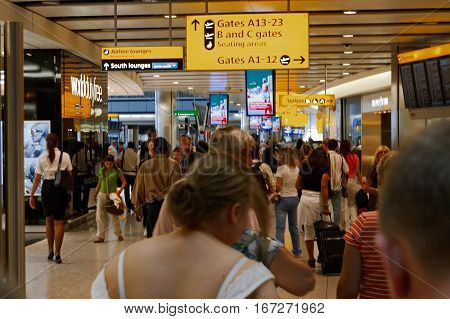 London, UK, 03 Jul. 2009: Many passengers walking toward A13-23 Gates in Heathrow Airport. Different direction and AD banners about.