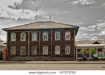 Yalutorovsk, Russia - May 27, 2006: Women wait for bus on stop near old house on Revolution street 55
