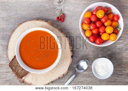 Tomato soup with dried herbs chilli tomoatoes and cream on the dark wooden table