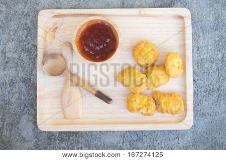 Chicken nuggets with ketchup on wooden tray