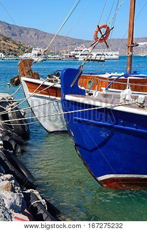 Greek fishing boats moored in the harbour Elounda Crete Greece Europe.