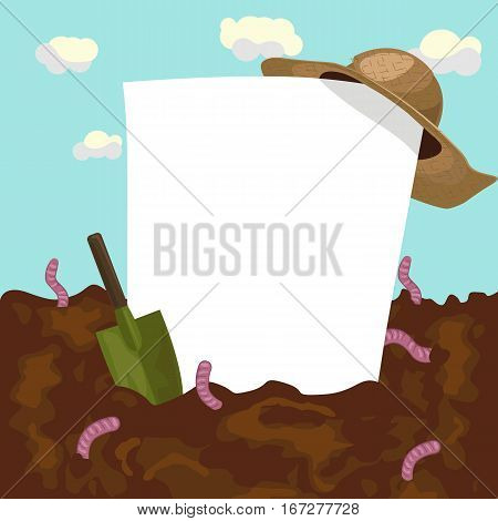 An empty blank board with straw hat and garden trowel on ground with earthworms