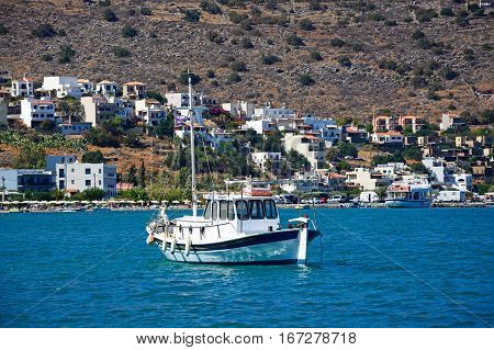 ELOUNDA, CRETE - SEPTEMBER 17, 2016 - Small yacht moored in the bay with buildings on the coastline to the rear Elounda Crete Greece Europe, September 17, 2016.