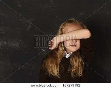 sweet young little schoolgirl in uniform covering her face with her arm crying sad victim of bullying at school isolated standing in front of dark blackboard in childhood and education problem concept