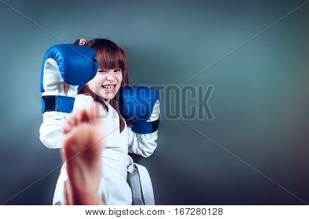 Girl wearing a karate uniform and blue boxing glove