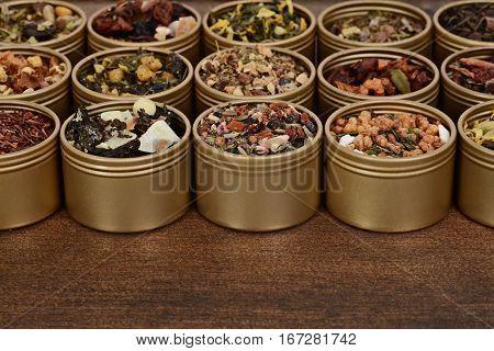 closeup herbal tea in tins on wood table