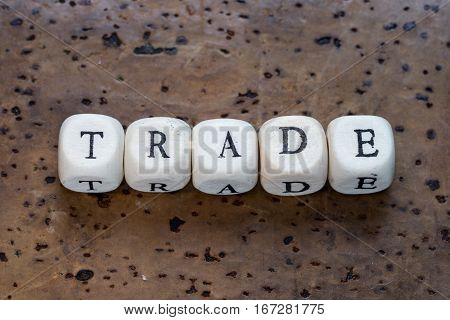 Trade Text On A Wooden Cubes On A Brown Cork Background