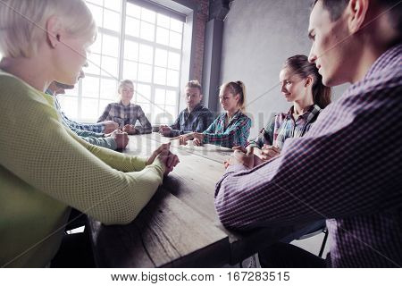 Team of people in casual clother working together sitting around wooden table and pointing at center startup concept