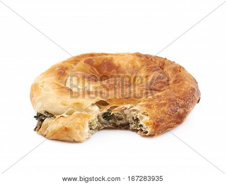 Cheese and spinach pastry bun with a bite taken off it, composition isolated over the white background