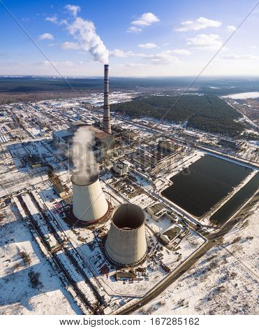 Heat electric station in winter. Aerial view. From above. Power station in a forest in sunny weather.