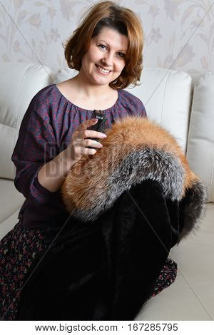 woman caring for a fur coat from natural fur