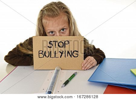 young beautiful schoolgirl scared in stress holding paper with text stop bullying written looking desperate asking for help sitting at school desk alone in victim children bullied and abuse concept