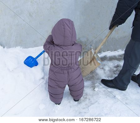 Father and baby together to clean up the snow shovels.