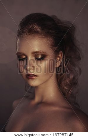 Glamour portrait of young fashion woman face with bright evening golden make up for party. Warm toning