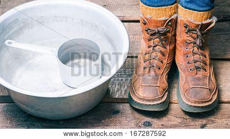 Feet wearing winter fur boots and wool socks near basin on the floor before footbath. Color toning